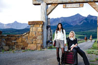 two women modeling fall fashions before a dramatic mountainscape