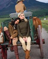 two women modeling fall fashions on the back of a wagon
