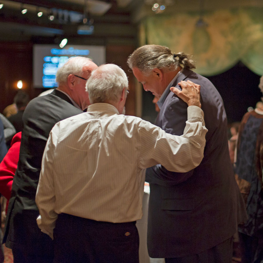A group of three men talking in a circle at the 2017 LEAP benefit.