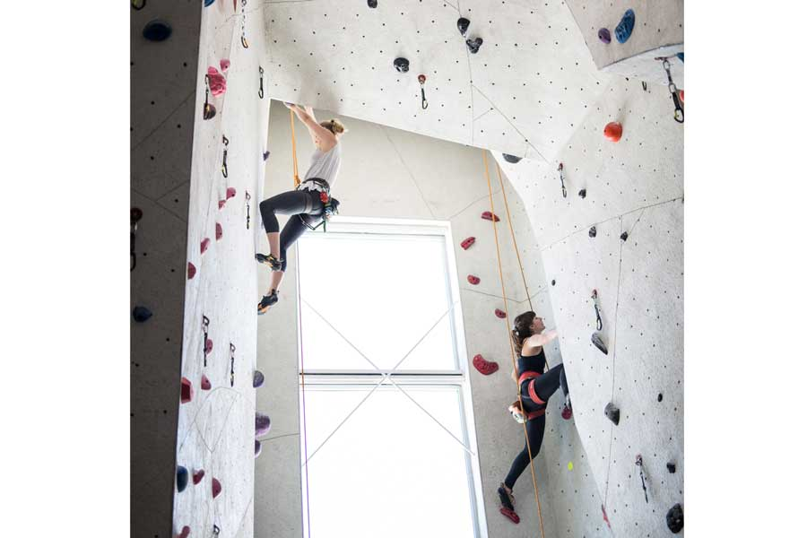 Two girls rock climbing at Vertical Endeavors