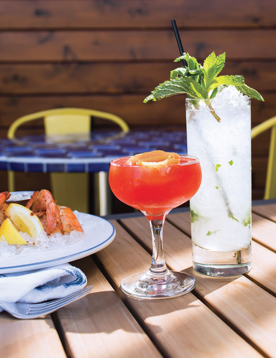 Two cocktails sitting on a tail next to a plate of shrimp on ice.