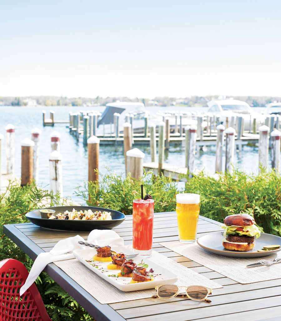 A shot of a table at 6Smith overlooking Lake Minnetonka that has a cheeseburger and beer alongside a fruity cocktail and other food offerings.