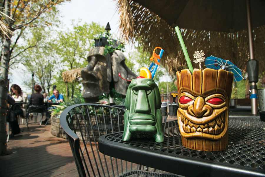 Cocktail drinks in tiki mugs sitting on a table on the patio at Psycho Suzi's.