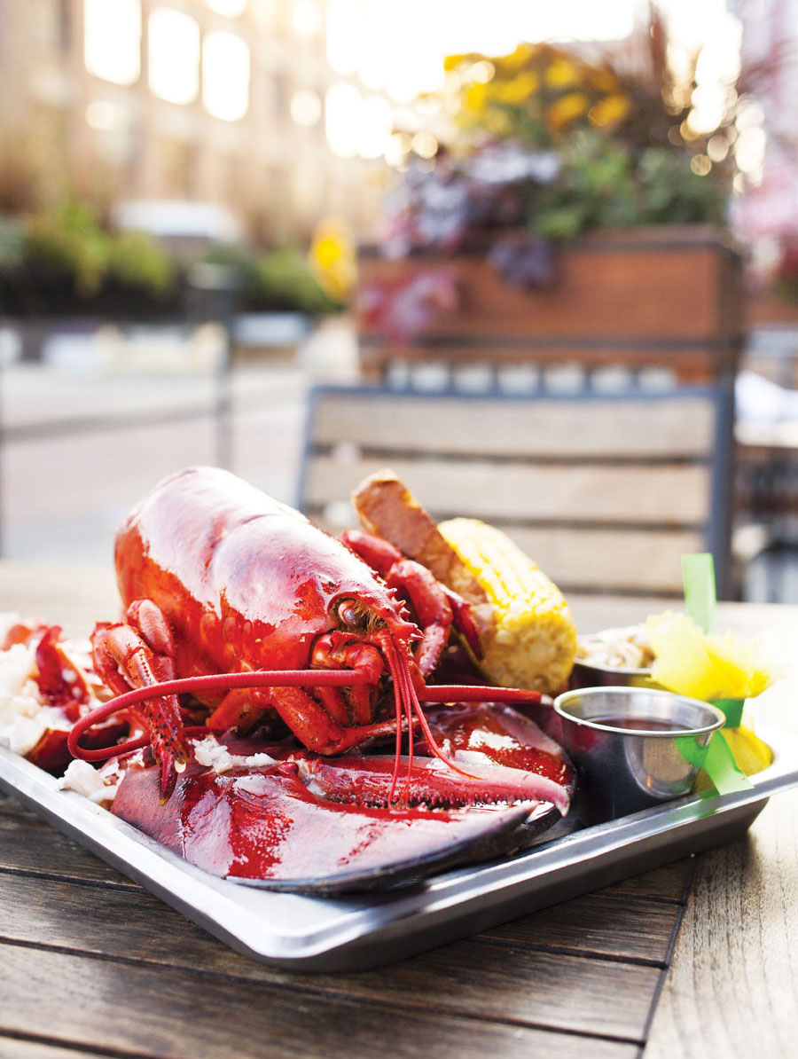 A plate consisting of a full lobster with an ear of corn on a table at Smack Shack's patio.