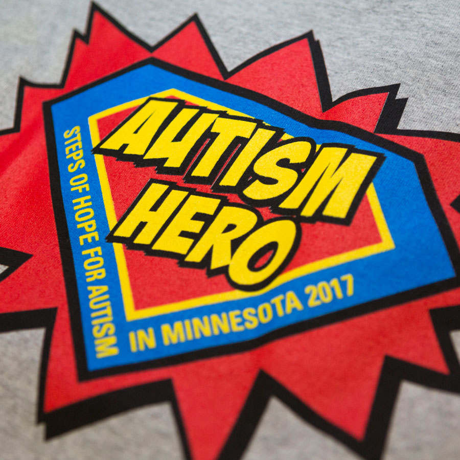 """A super hero logo in the shape and color of the Superman logo with the words """"Autism Her"""" in the center."""