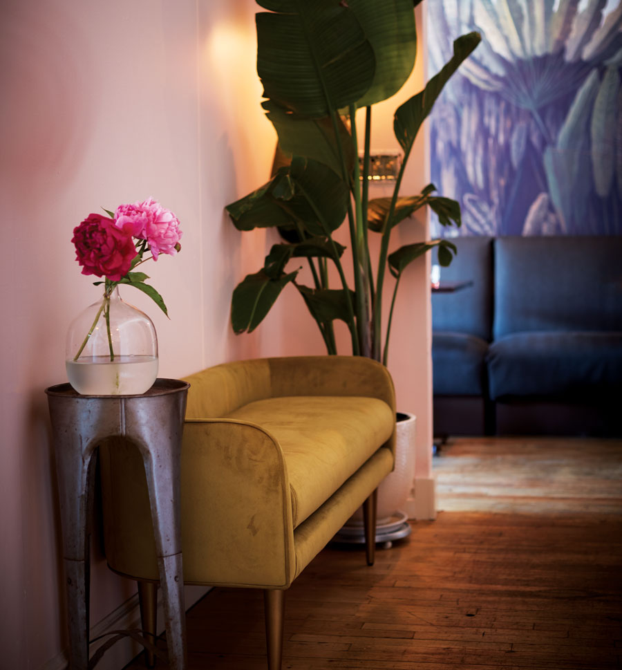 A vase of flowers is set next to a couch in the interior of Grande Cafe in Minneapolis.