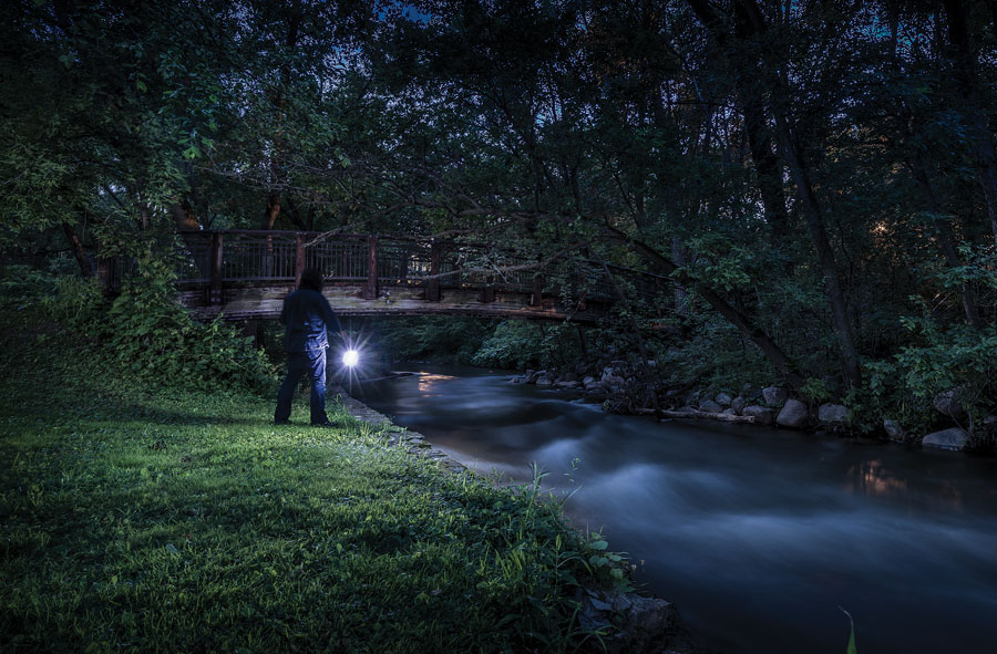 A man with a flashlight exploring a creek with a bridge extending over it at night.