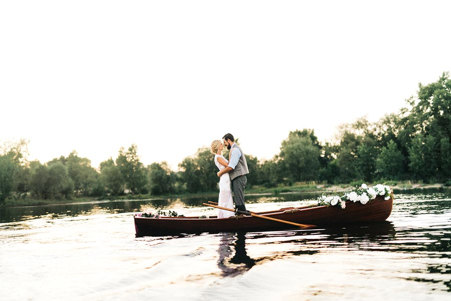 A newly wed couple standing in a canoe in the middle of a lake.