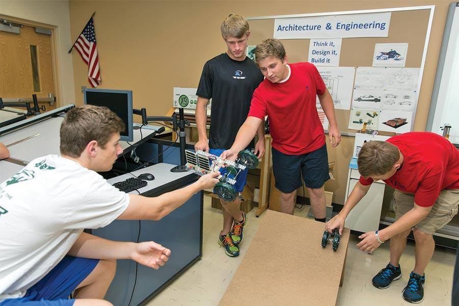 Four boys testing car designs at a STEM school.