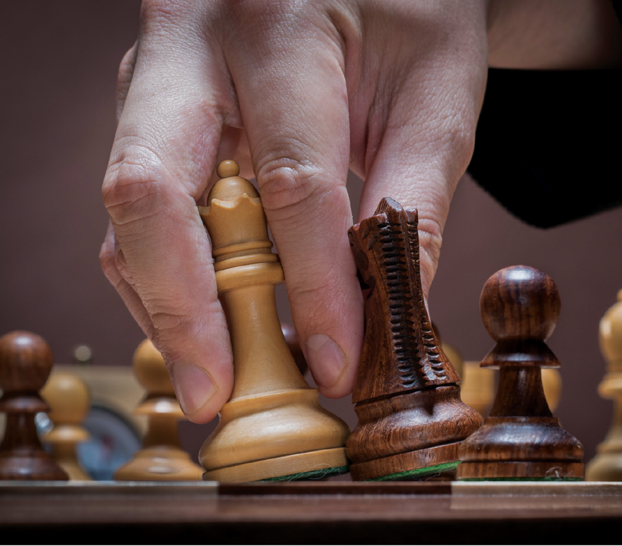 A close-up of Wesley So's hand grabbing the chess pieces of a queen and knight.