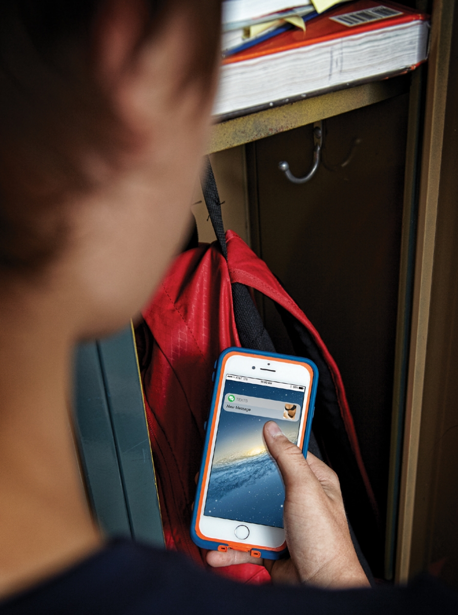 A boy standing at his locker is holding his phone showing he received a new message containing a picture of a girl in her underwear.