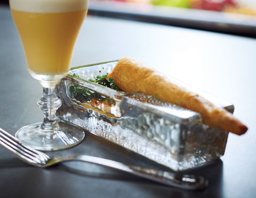 Gray Duck Tavern's Cuban Cigar, a crispy tortilla wound around pork and served on a glass tray with a tart.
