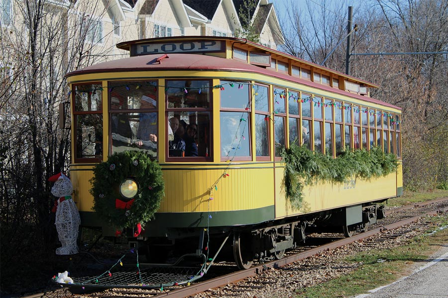 The Excelsior Christkindlsmarkt trolley on tracks outside of an apartment complex.