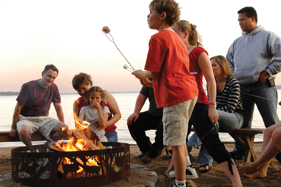 A family sitting around a campfire by a lake roasting marshmallows at Grand View Lodge in the Brainerd Lakes area.