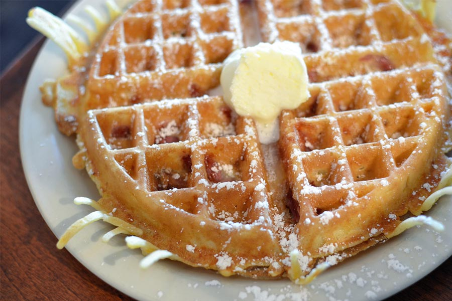 A Meat Waffle from Hazel's Northeast in Minneapolis covered in butter and powdered sugar.