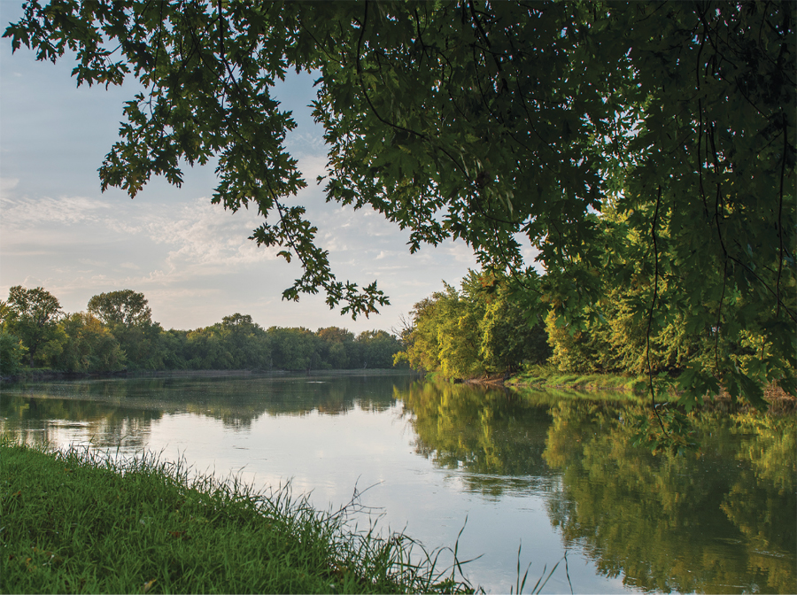 A river surrounded by lush greenery in the afternoon at Sioux Agency State Park.