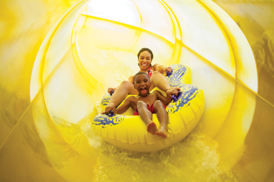 A mom and her son riding down a yellow waterslide at Great Wolf Lodge in Bloomington, Minnesota.