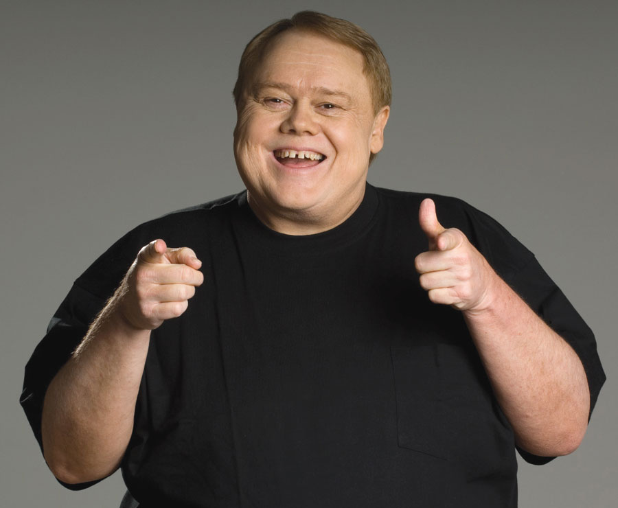 Louie Anderson smiling and fingergunning the camera.