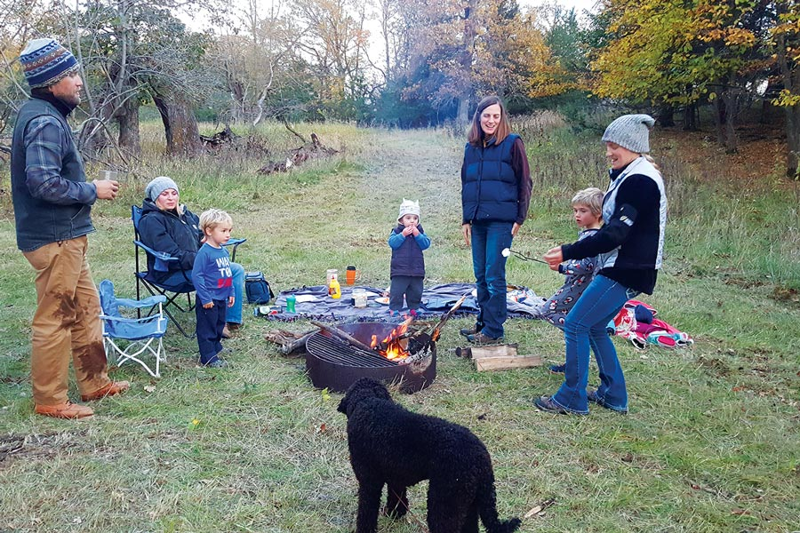 A family roasting marshmallows around a campfire at a campsite.