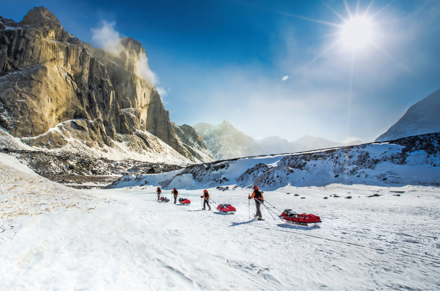 Will Steger, Ann Bancroft and Dan Buettner pulling sleds through a frozen, mountainous area.