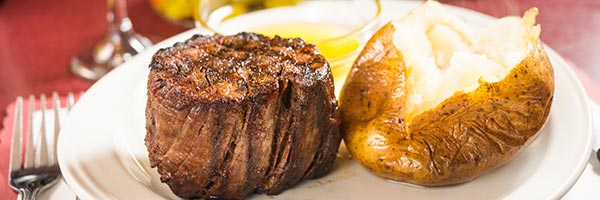 A steak and baked potato on a plate at Mancini's in St. Paul, Minnesota.