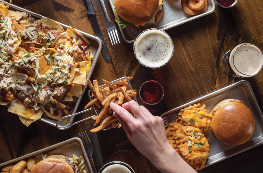 A table full of food, including fries, burgers and nachos.