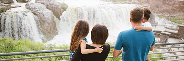A family watching the waterfalls at Sioux Falls, SD.