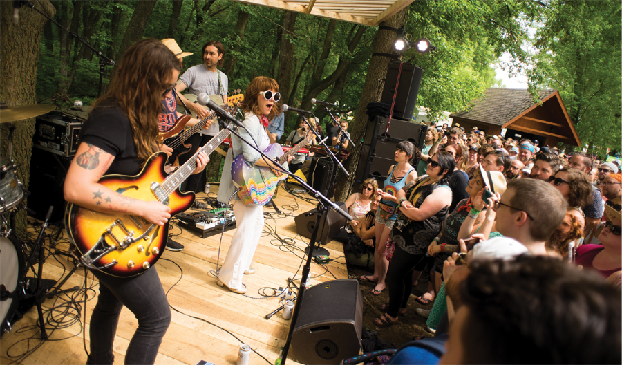 Jenny Lewis, front and center, performs with a band of white guys with guitars at Eaux Claires in 2017.