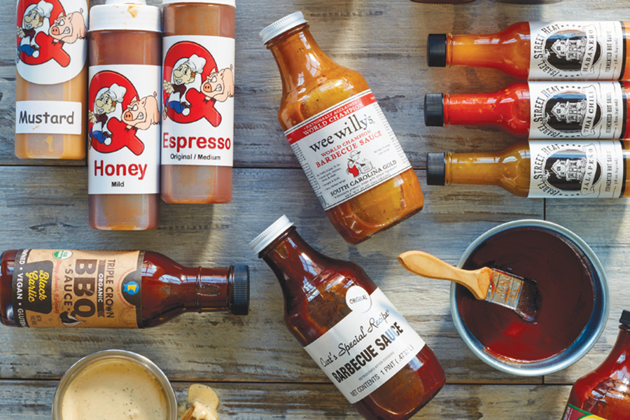 A collection of barbecue sauces laid out on a wooden background.