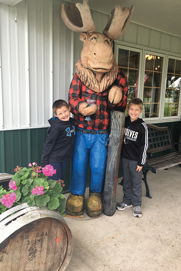 Two boys taking a picture next to a moose statue at Carlos Creek Winery in Alexandria, Minnesota.