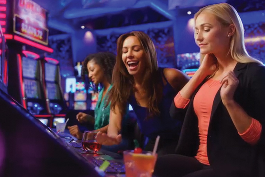 Two girls playing the slot machines at Treasure Island Resort & Casino.