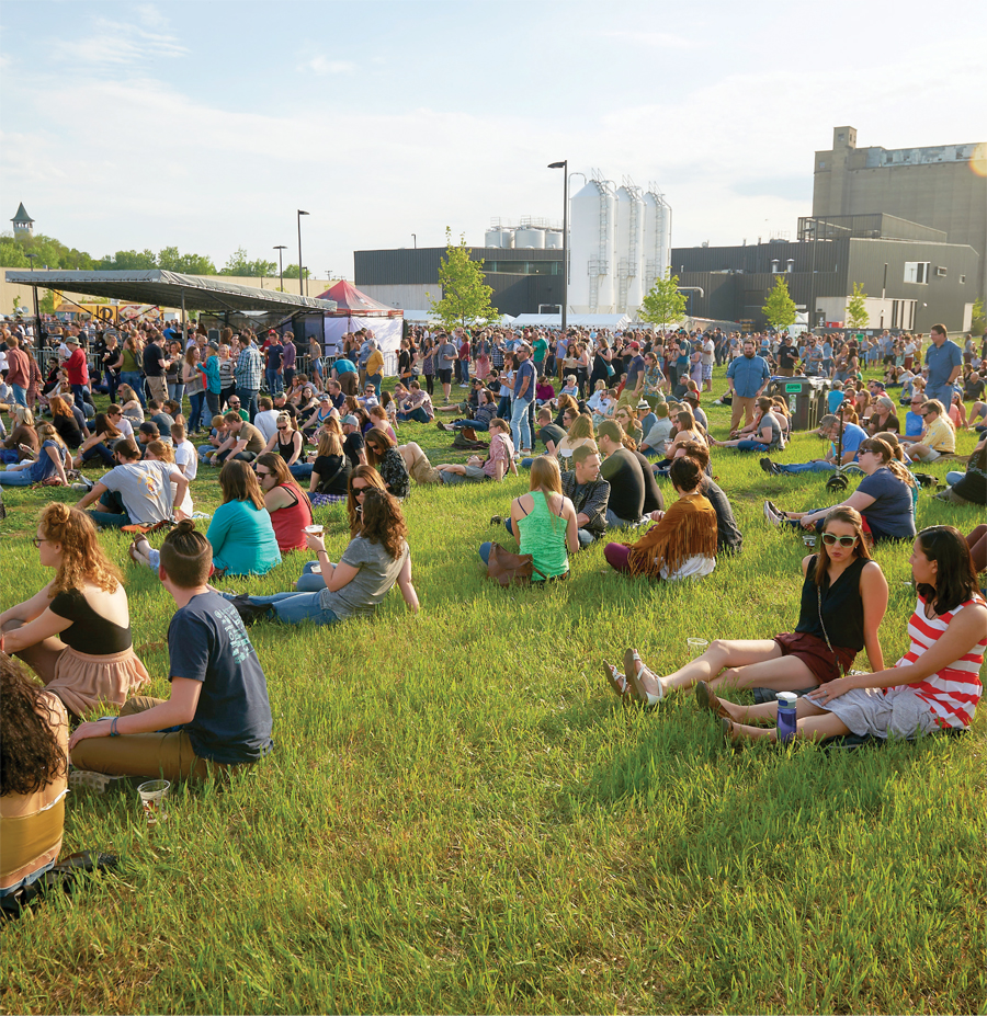 People sitting in the grass enjoying music at the Surly Festival Field.