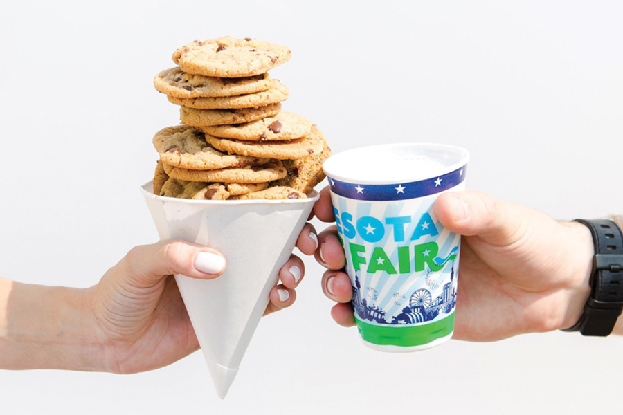 A cup of Sweet Martha's Cookies next to a glass of milk from the Minnesota State Fair.