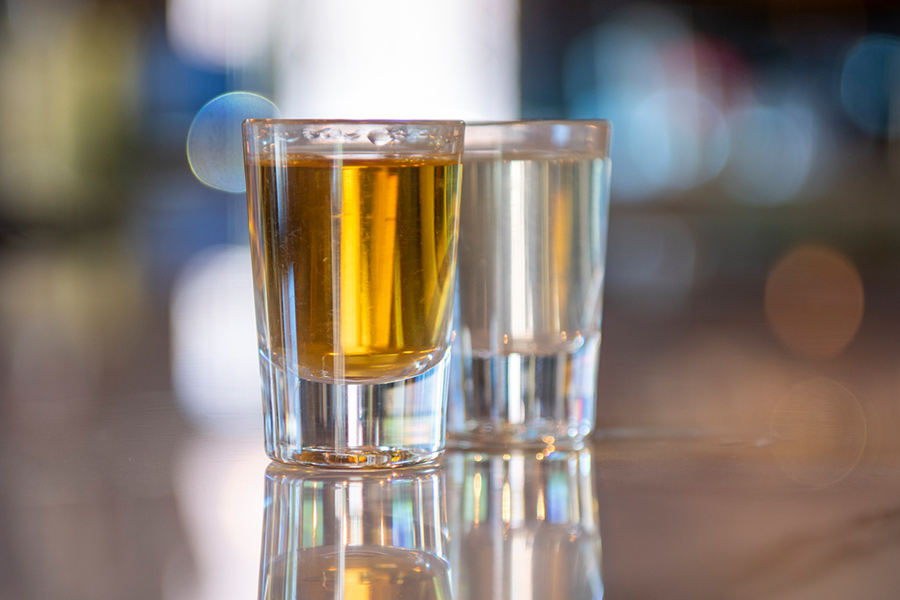 Two glasses of alcohol on a bar.