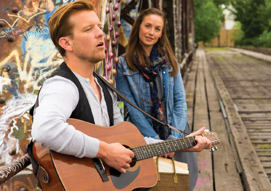 A man serenading a girl with a guitar on a railroad track in a production of Once.