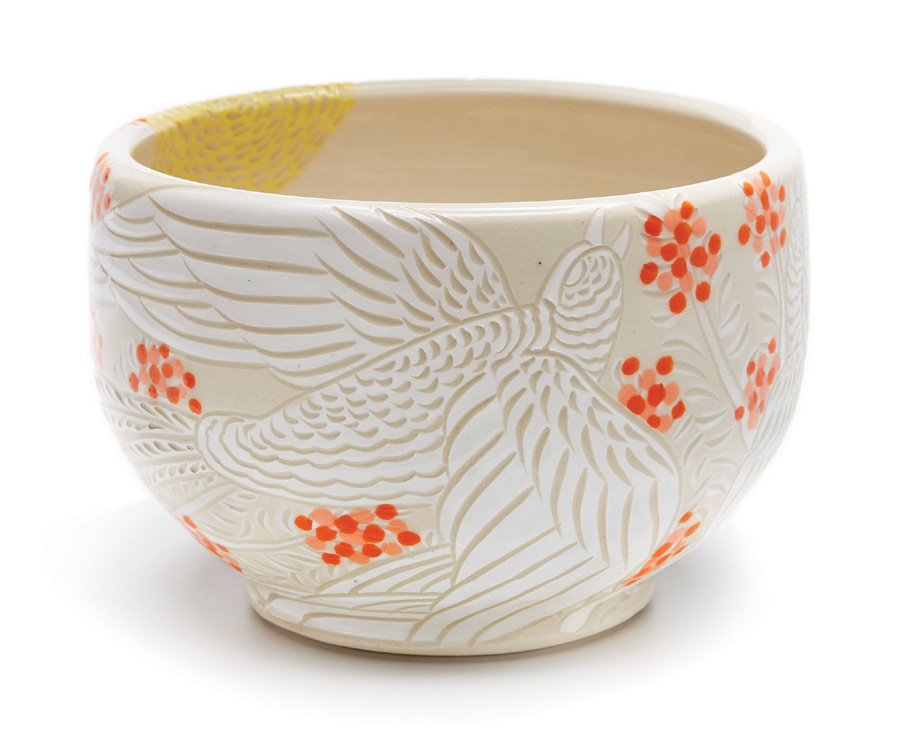 A white bowl with a bird and flower designs at the American Pottery Festival.