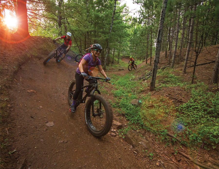 People biking on Cuyuna Mountain Bike Trail System's trails.