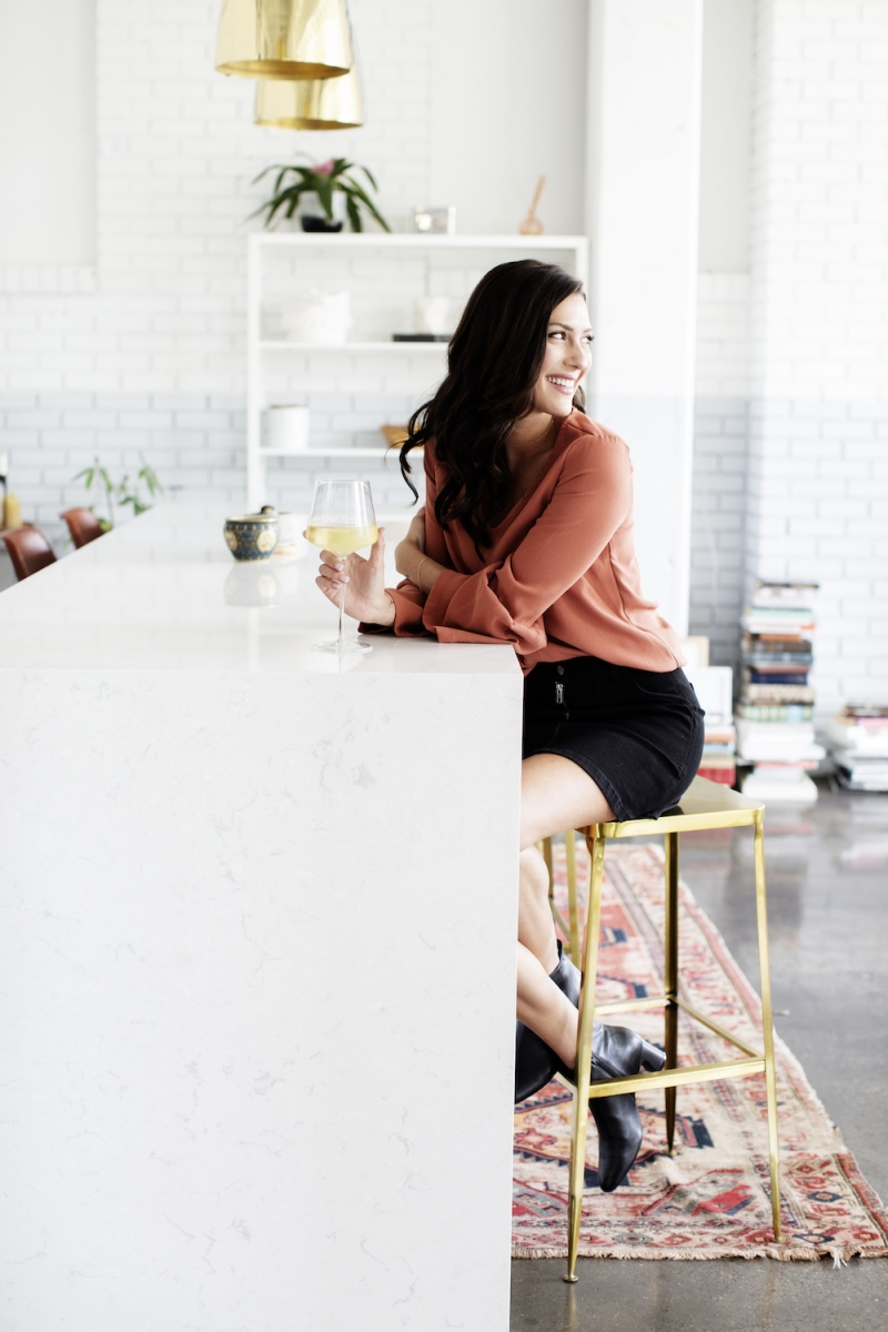 Becca Kufrin sitting at a kitchen island with a glass of wine.