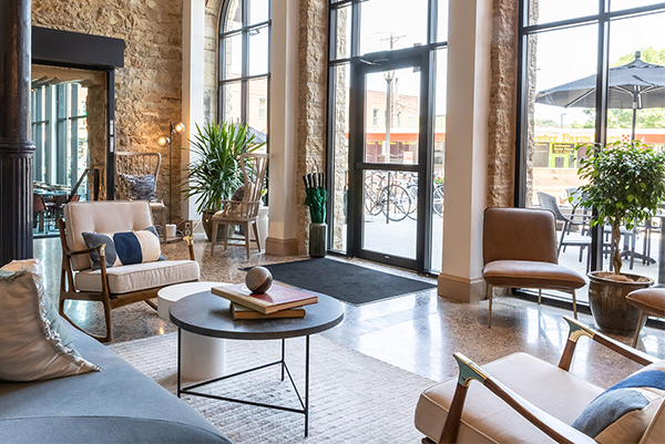 Hotel lobby with exposed stone walls and modern furniture at Lora Hotel in Stillwater