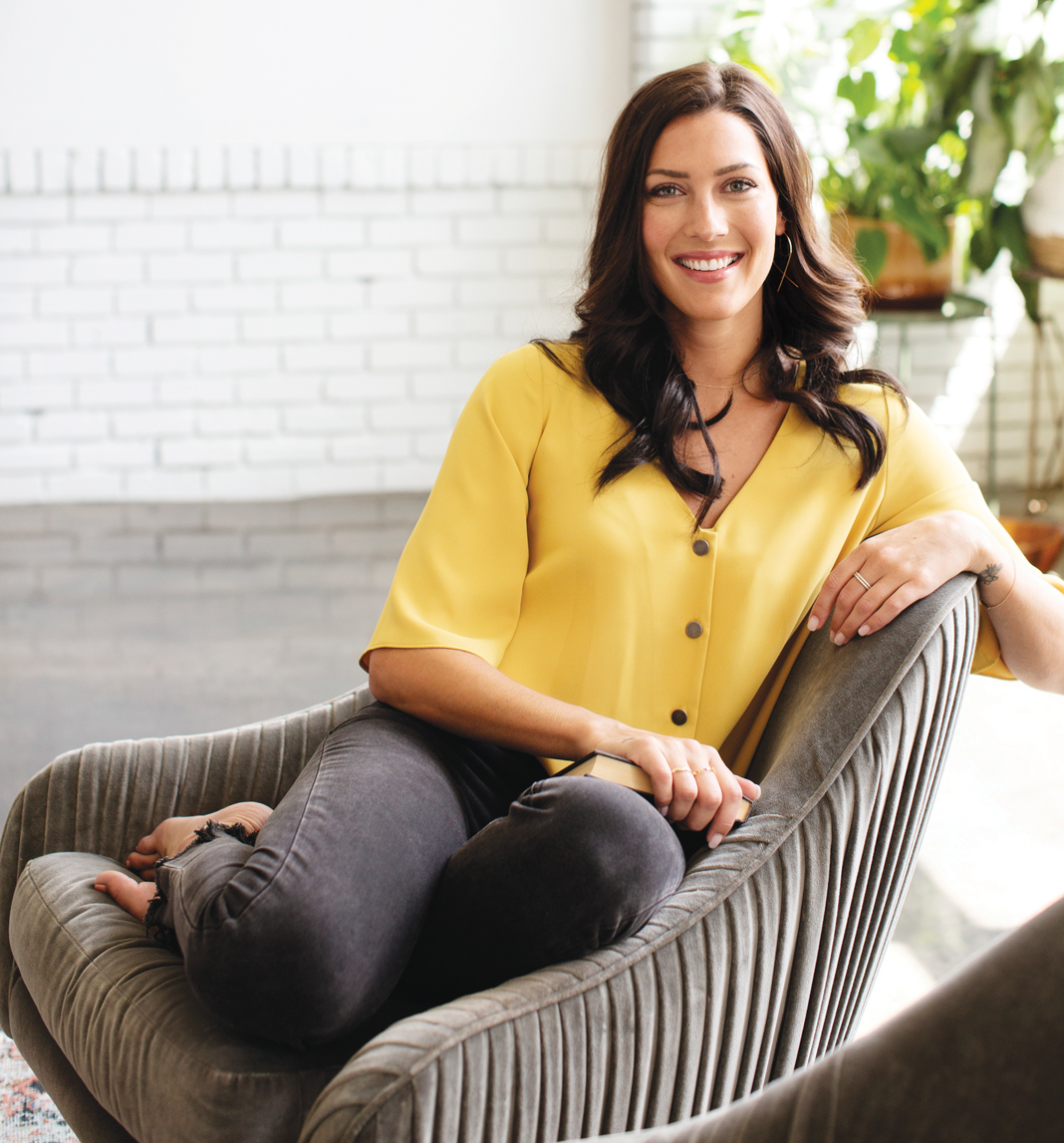 A portrait of Becca Kufrin sitting on a couch.