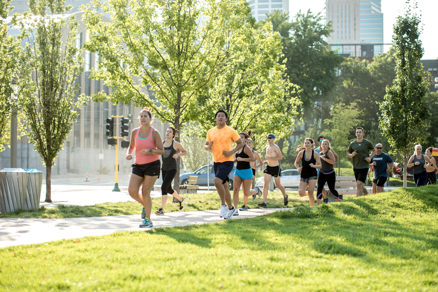 A group of people running outside U.S. Bank Stadium during a class at Fly Feet Running.