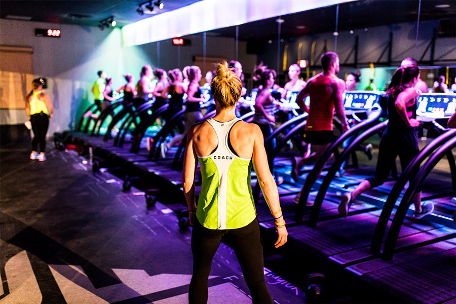 A class with people running on treadmills at Fly Feet Running.