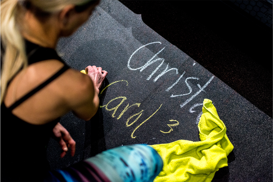 A girl writing her name in chalk on the floor at Fly Feet Running.