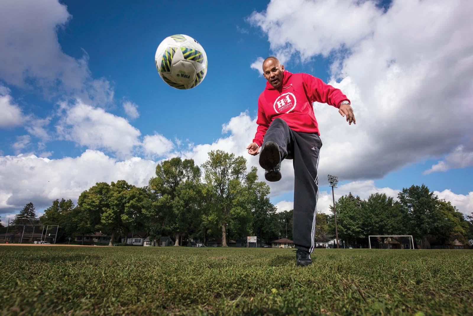Tony Sanneh kicking a soccer ball.