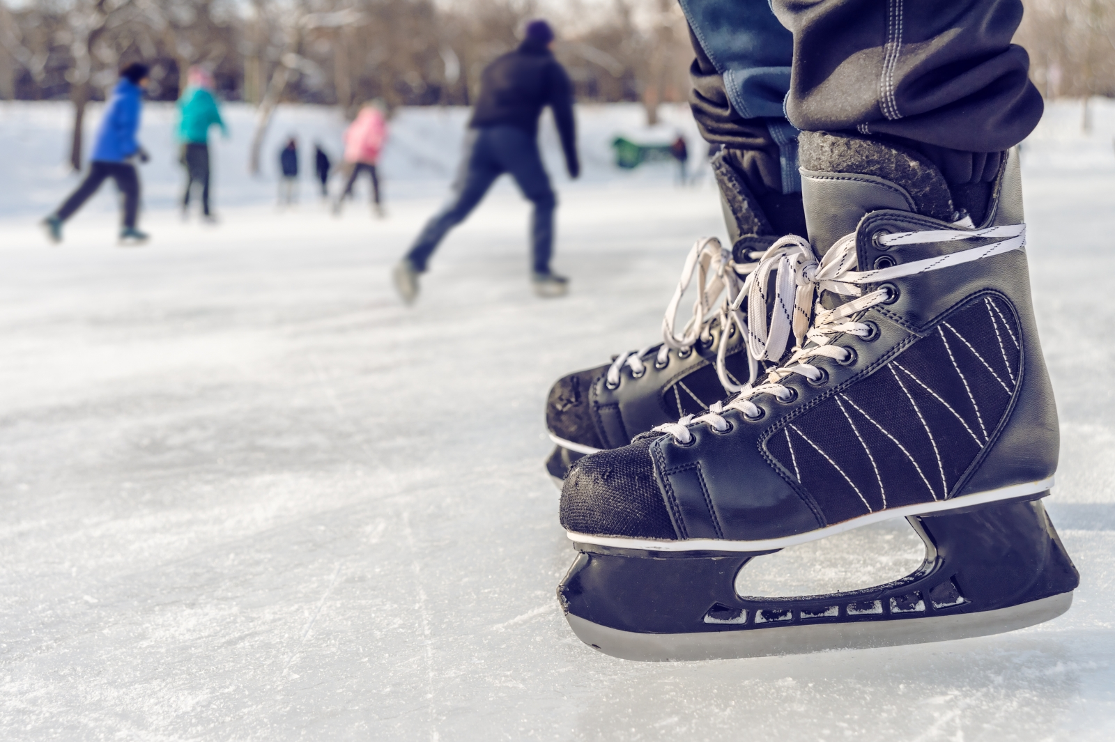 A hockey skater stands on the ice outside. Photo by mbruxelle/Fotolia.