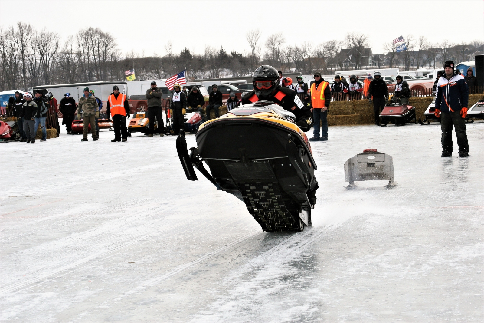 "A snowmobile driver lifting up the front of the sled in a ""wheelie"" at the Waconia Ride-In. Courtesy Waconia Ride-In."