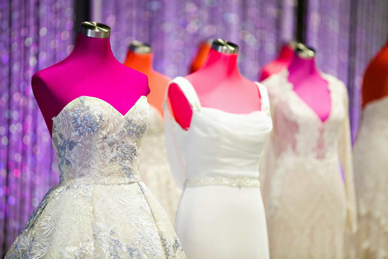 A line of wedding dresses on mannequins at a past Twin Cities Bridal Show. Photo by Lauren B Photography, courtesy The Wedding Guys.