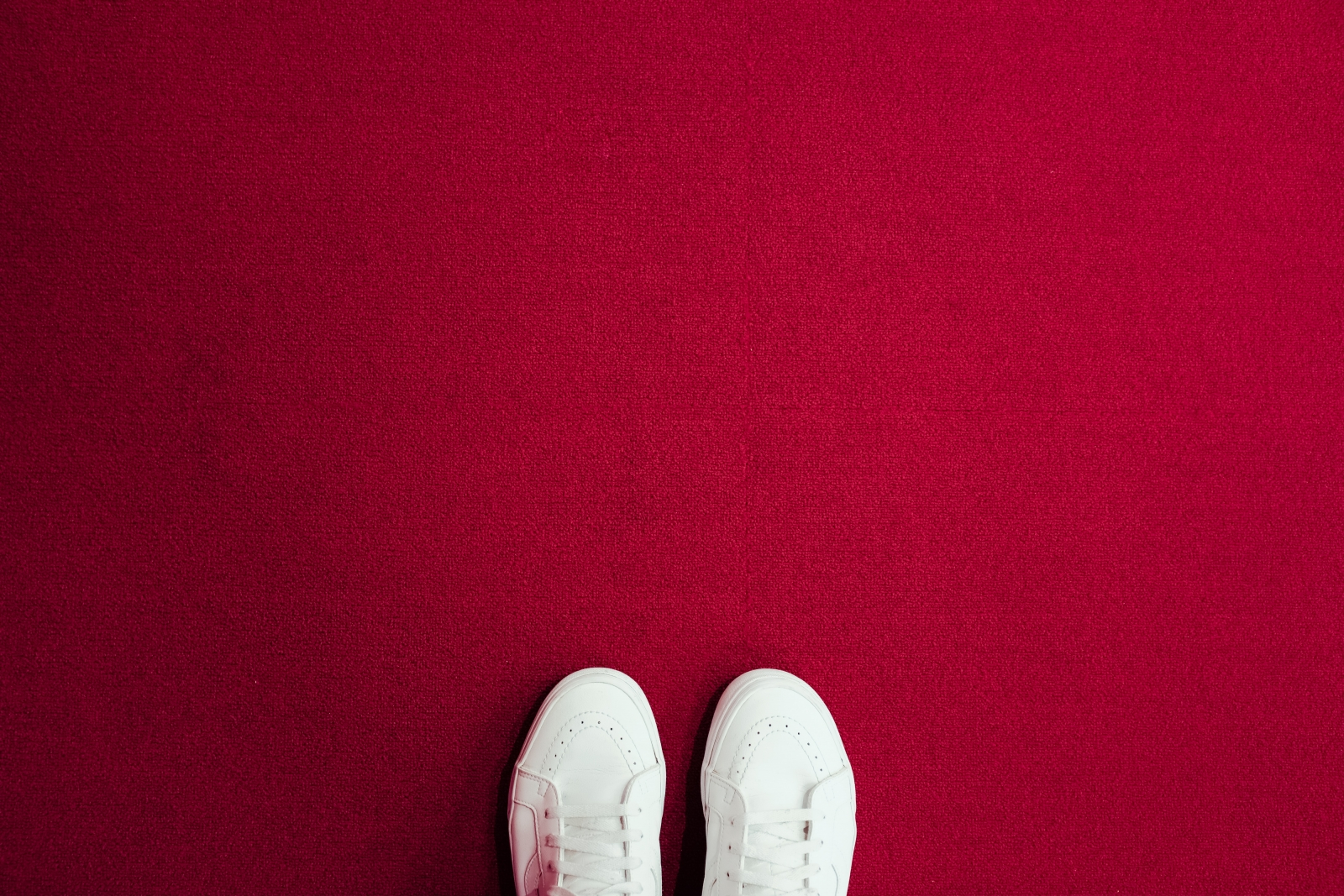White sneakers on a red carpet. Photo by Christian Chen/Unsplash.