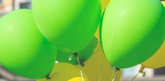 Bright yellow and green balloons on a city street event in summer. Close up shot