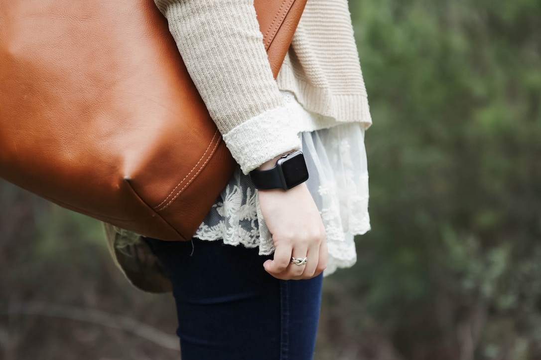 A woman with a smartwatch in the park with a leather shoulder bag